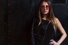 Фото моды привлекательной женской модели в агрессивных одеждах стиля утеса и розовых солнечных очках представляя в темном интерье стоковое фото
