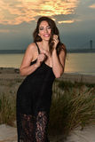 Фото моды сексуальной модели очарования в черном платье шнурка представляя довольно на пляже Стоковое Изображение