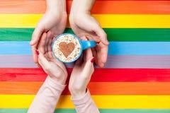 Фото мужских и женских рук держа чашку кофе на wond Стоковые Фото