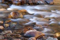 Фото нерезкости движения воды пропуская над округленными утесами Стоковое фото RF