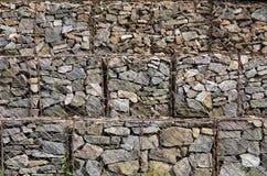 Фото нескольких gabions Клетки сетки кубовидной формы заполнены с камнями горы различных форм которые позволяют throu воды стоковые изображения