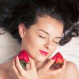 Фото обольстительной женской держа клубники около губ стороны, ягоды чувственной женщины redhead портрета крупного плана сдержива Стоковые Фото