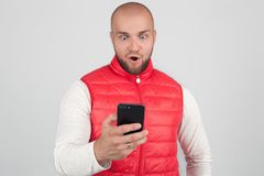 Фото оглушенного мужчины читает текстовое сообщение с удивленным выражением, держит сотовый телефон, узнает что-то сотрясать, сое стоковые изображения