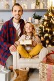 Фото отца и девушки с предпосылкой подарка украшений рождества в студии Стоковая Фотография RF