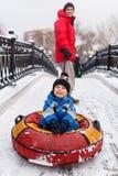 Фото отца катаясь на коньках сына на трубопроводе в парке зимы Стоковая Фотография