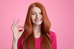 Фото положительной женщины имбиря с длинными волосами, выставками одобряет символ над розовой предпосылкой, выражает ее утвержден Стоковое фото RF