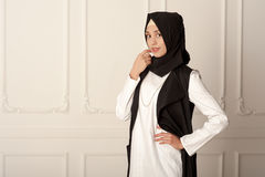 Фото появления у молодой женщины ближневосточного современные мусульманские одежды и черный шарф Стоковые Изображения
