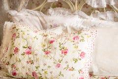Фото подушки с флористической печатью на большой кровати Стоковые Изображения RF