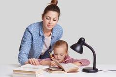 Фото представления матери и daugher на рабочий стол совместно, данные по wrtite в тетради, прочитало много книг, подготавливает д стоковое изображение rf