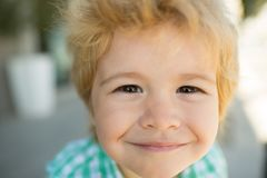 Фото прелестного молодого счастливого мальчика смотря камеру Счастливый смешной конец стороны ребенка вверх Супер улыбка от ребен стоковая фотография rf