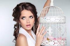 Фото принципиальной схемы изумленной женщины держа винтажную клетку птицы изолированный Стоковое Изображение