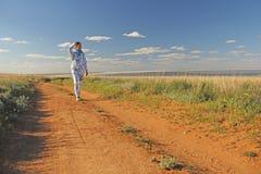 Фото принятое в лето Девушка идет на дорогу против t Стоковые Изображения RF