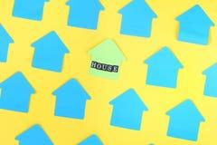 Фото пустых голубых стикеров на желтой предпосылке Стикеры в форме дома лежат раскосно В центре там Стоковое фото RF