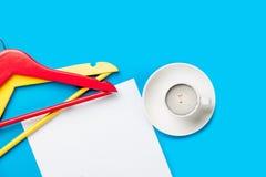 Фото пустых листа бумаги, чашки кофе и вешалок на Стоковые Изображения RF