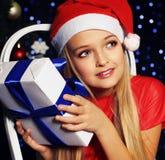 Фото рождества милой маленькой белокурой девушки в шляпе santa и красном платье Стоковая Фотография RF