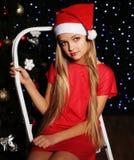 Фото рождества милой маленькой белокурой девушки в шляпе santa и красном платье Стоковые Изображения RF