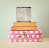Фото розового чемодана с polkadots и стог книг над деревянным столом, ретро изображением стиля Стоковое Изображение RF
