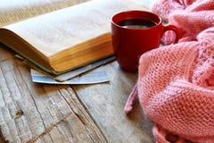 Фото селективного фокуса розового уютного связанного шарфа с к чашкой кофе, шариками пряжи шерстей и открытой книгой на деревянно стоковые изображения