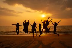 Фото силуэта торжества команды на пляже на заходе солнца стоковые фотографии rf