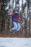 Фото скача женщины с рюкзаком идя в лес зимы Стоковые Фото