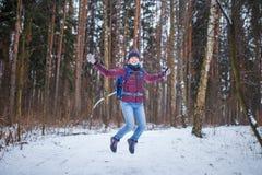 Фото скача женщины с рюкзаком идя в лес зимы Стоковые Изображения RF