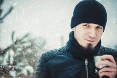 Фото сконцентрированного thermos удерживания шляпы бородатого человека нося в руках стоя в лесе стоковые фотографии rf