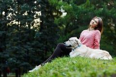 Фото снизу женщины сидя с собакой на зеленой лужайке Стоковые Изображения