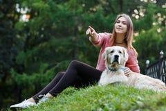 Фото снизу женщины указывая вперед рядом с собакой на зеленой лужайке Стоковое Фото