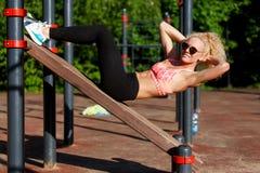 Фото солнечных очков женщины спорт нося тренируя прессу в парке Стоковое Изображение