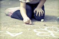 Фото сочинительства девушки с мелом на школьном дворе Стоковые Фотографии RF