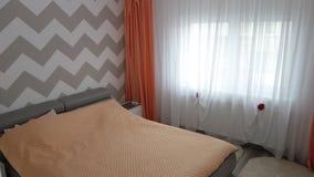 Фото средней квартиры спальни размера в серых цветах, кожаной современной и минималистской кровати, белом офисе и комоде, стеклян Стоковые Фотографии RF