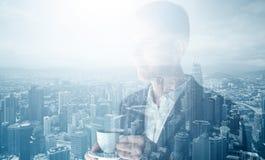 Фото стильного взрослого бизнесмена нося ультрамодный костюм и держа кофе чашки Двойная экспозиция, город сверстницы панорамного  Стоковая Фотография RF