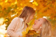 Фото стороны девушки с мамой в парке осени в после полудня стоковые изображения rf