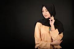 Фото студии типа красивой молодой женщины восточного без сокращений, на темной предпосылке, одетой в мусульманском стиле Стоковое Фото