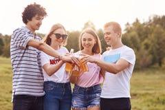 Фото счастливых подростков празднует что-то или как раз имеет остатки внешние, clink бутылки пива, услаждало выражения, носку su стоковое фото rf