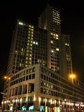 Фото с предпосылкой ночи современных архитектурноакустических многоэтажных зданий офиса и гостиничного комплекса Стоковое Изображение