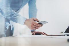 Фото телефона родового дизайна умного держа в руках бизнесмена запачканная предпосылка горизонтальный модель-макет Стоковые Изображения RF
