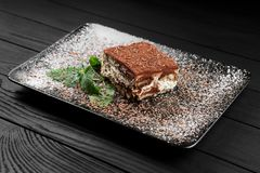Фото торта тирамису и мята листают на черной деревянной предпосылке Стоковое Изображение RF