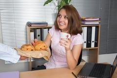 Фото усмехаясь бизнес-леди брюнет работая и имея завтрак Стоковое фото RF