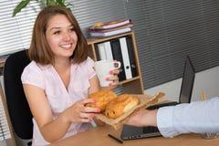 Фото усмехаясь бизнес-леди брюнет работая и имея завтрак Стоковое Изображение RF
