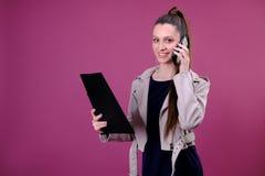 Фото успешной доски сзажимом для бумаги удерживания женщины 20s с файлами в офисе и говорить на мобильном телефоне над розовой пр стоковая фотография rf