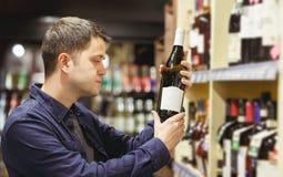 Фото человека брюнета с бутылкой вина около полок с бутылками стоковые фотографии rf