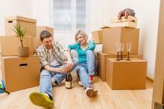 Фото человека с бутылкой вина и женщины сидя на софе среди картонных коробок Стоковое Изображение RF