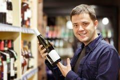 Фото человека с бутылкой вина около полок с бутылками стоковое фото rf