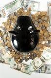 Фото черной копилки на куче монеток Стоковая Фотография