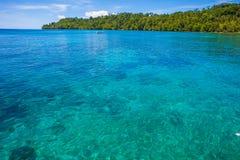 Фото человека управляя естественным деревянным океаном Вест-Инди шлюпки длинного хвоста Чистая вода и голубое небо с облаками гор Стоковая Фотография RF