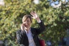 Фото элегантной бизнес-леди усмехаясь и говоря на телефоне стоковая фотография rf