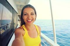 Фото Selfie молодой модельной женщины на роскошных каникулах круиза перемещения в желтом платье наслаждаясь вечером на побережье  Стоковые Изображения