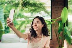 Фото selfie молодой азиатской женщины takeing используя smartphone дома Стоковое фото RF