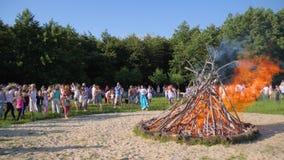 Фольклорные праздненства дальше под открытым небом на зеленом glade, толпе людей около большого большого balefire на природе, ярк видеоматериал
